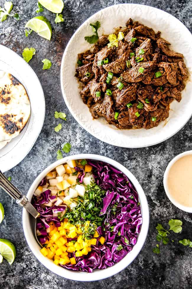 Beef Bulgogi and Pear Mango Slaw in separate white bowls for best Korean Tacos