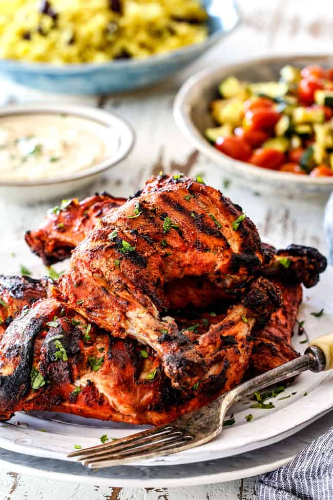 far away shot of Authentic Tandoori Chicken Recipe with marinated chicken legs stacked on a white platter