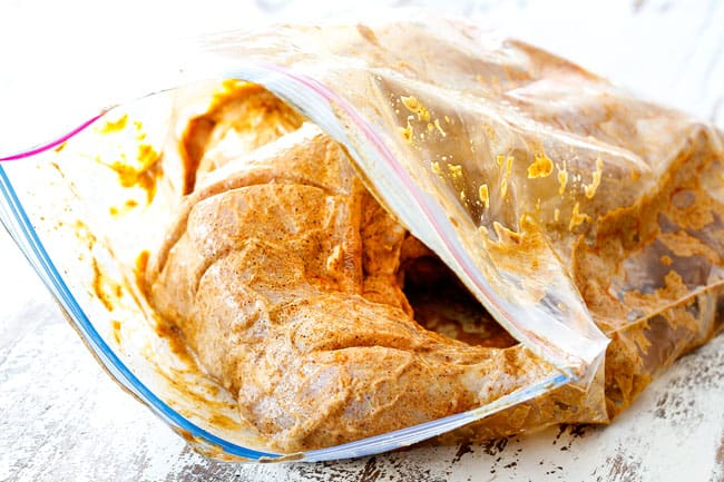 showing how to make Tandoori Chicken by adding chicken to marinade in a plastic bag