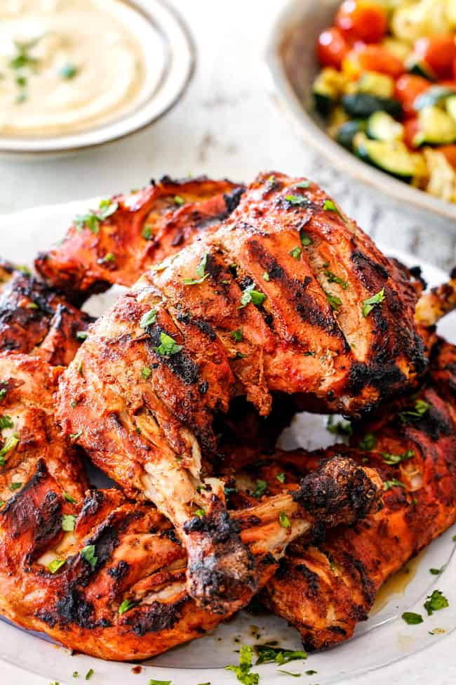Side view of authentic Tandoori Chicken Recipe with marinated and slashed chicken on a white platter with yogurt dip