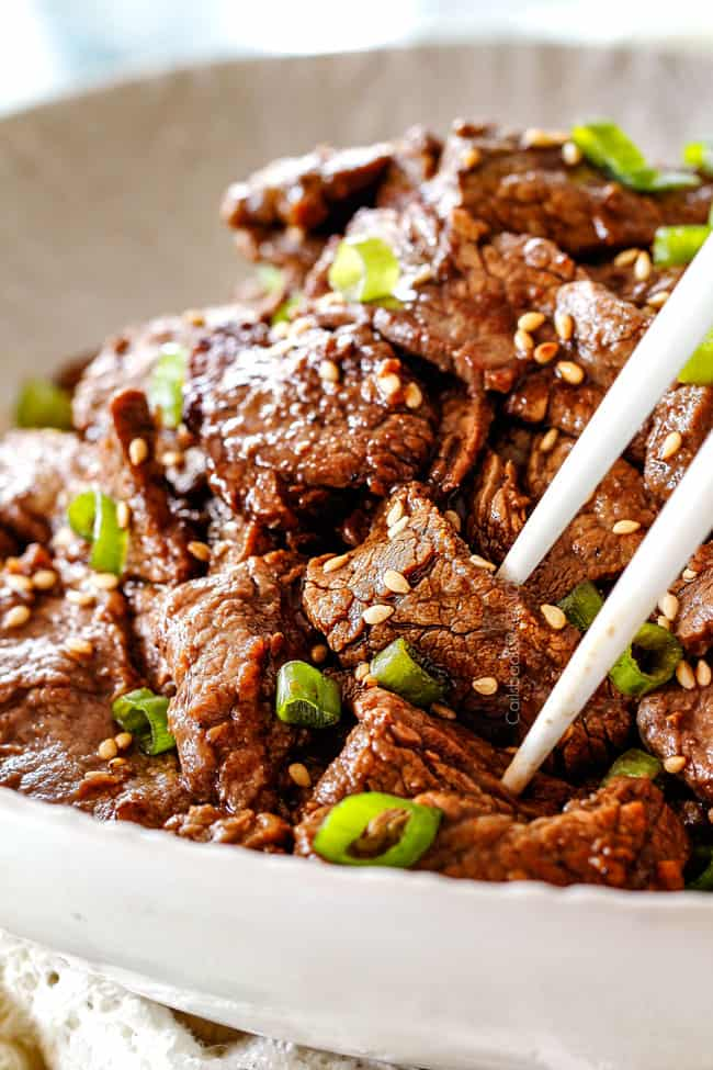 using chopsticks to pick up Beef Bulgogi in a white dish with sesame seeds and green onions