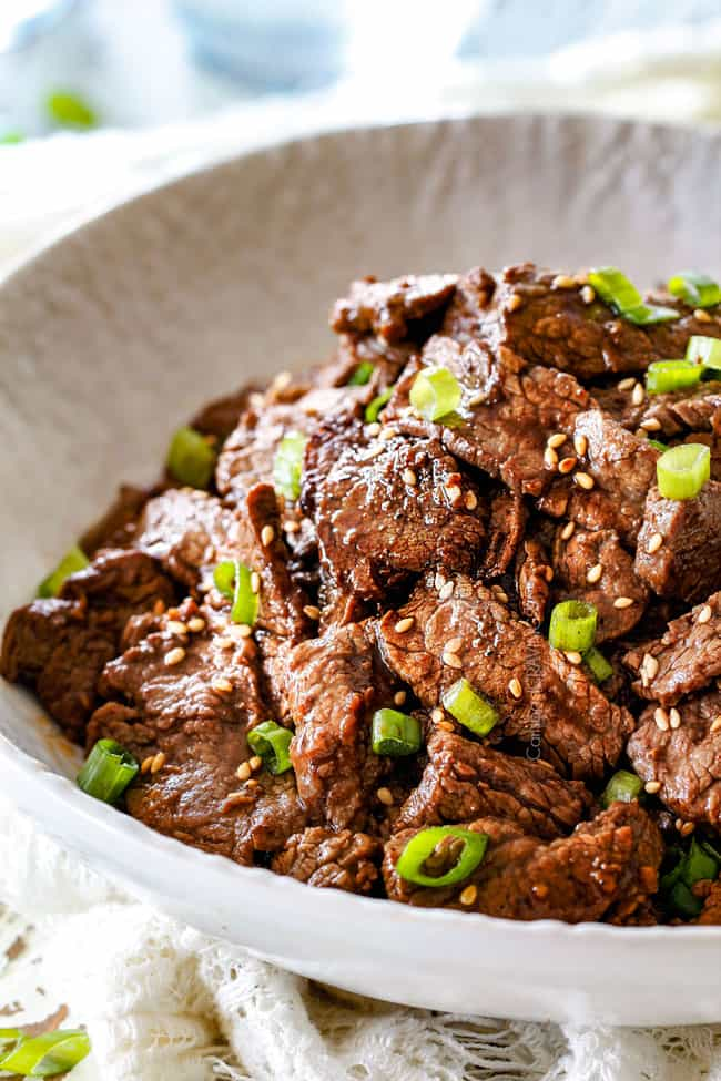 side view of authentic Beef Bulgogi recipe in a white dish with sesame seeds and green onions