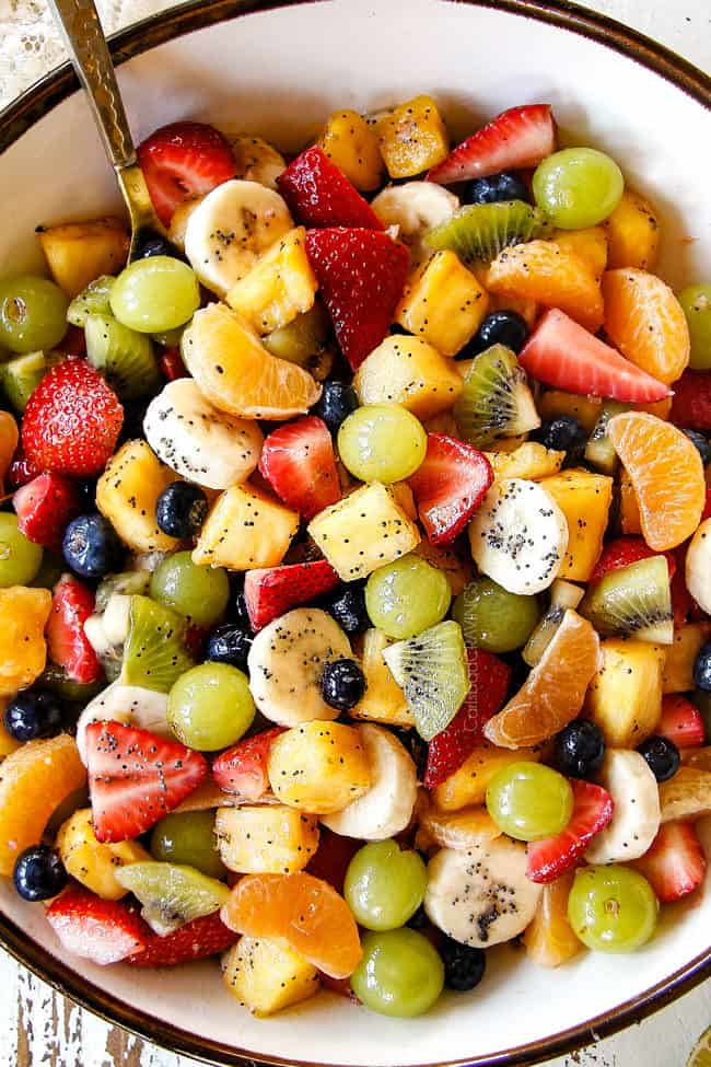 top view of best fruit salad in bowl with pineapple, strawberries, blueberries, bananas, kiwis, grapes and oranges