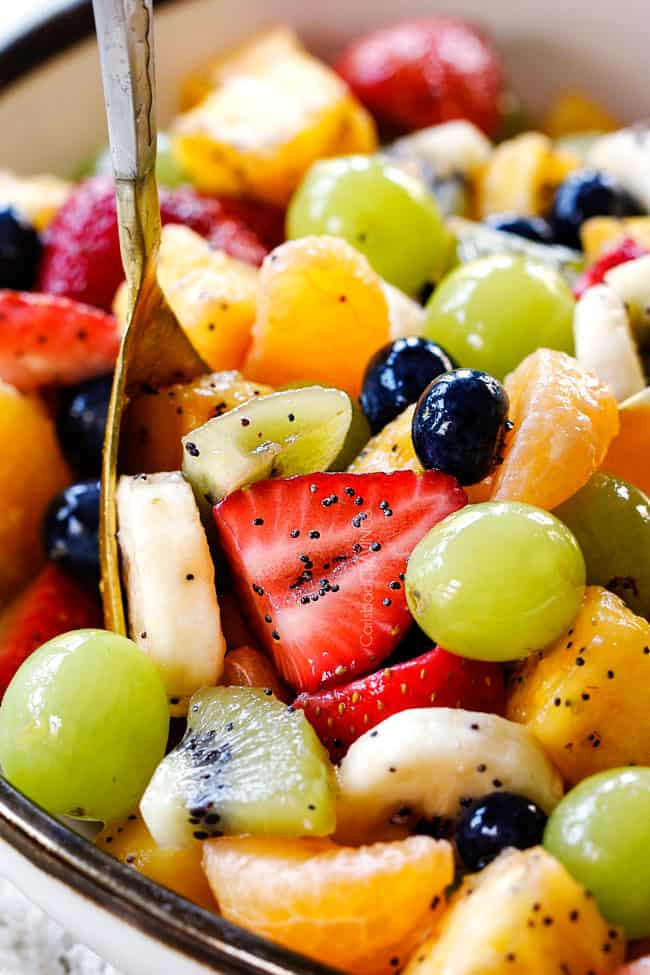 a gold spoon in a white bowl of easy fruit salad with pineapple, bananas, strawberries, blueberries, kiwis, oranges, pineapple