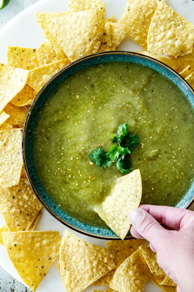 top view of dipping tortilla chip into a bowl of easy salsa verde