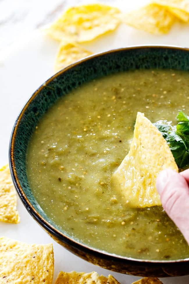 Dipping tortilla chip into a bowl of homemade salsa verde