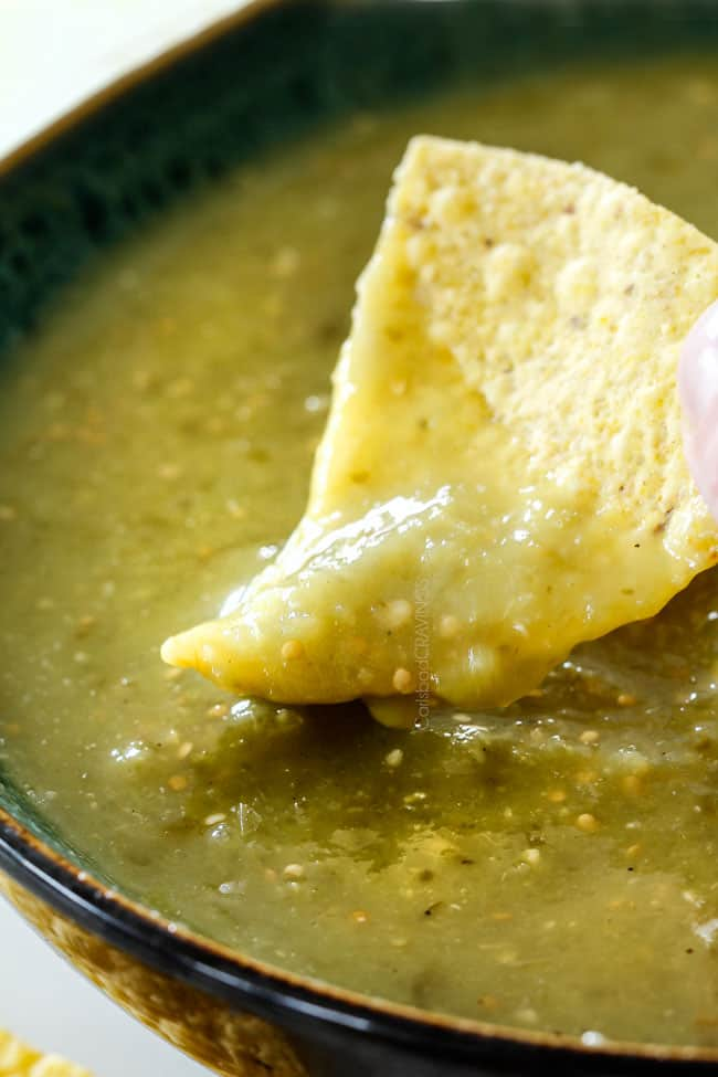 dipping tortilla chip into a bowl of best salsa verde