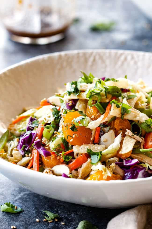 side view of top view of best ever Chinese chicken salad with ramen noodles, Mandarin oranges, peanuts napa cabbage, wontons, carrots, snow peas, red bell peppers all tossed together with sesame dressing