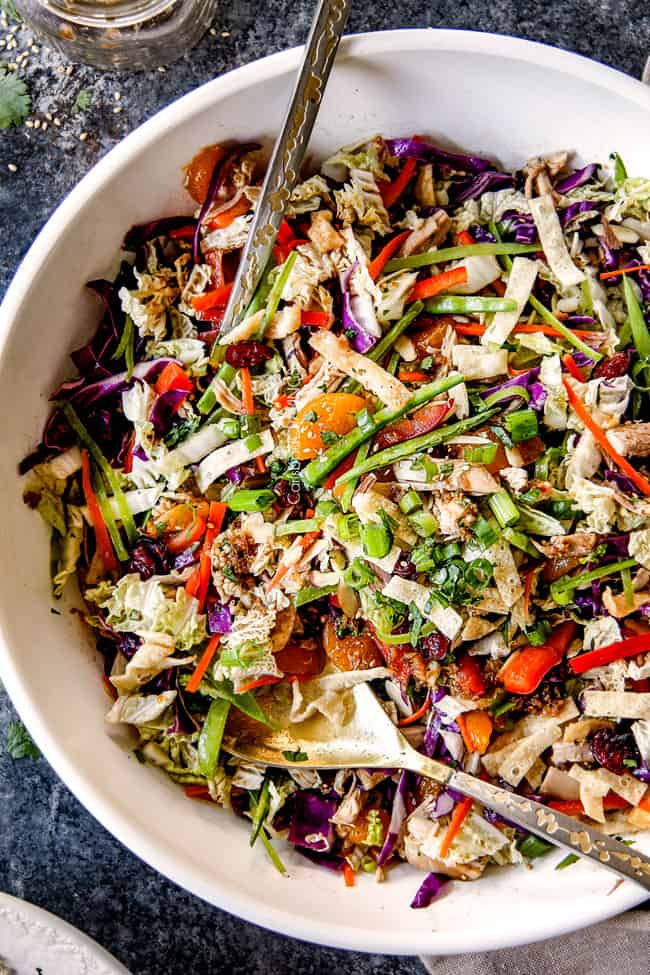 top view of best ever Chinese chicken salad tossed together with mandarin oranges, peanuts napa cabbage, wontons, carrots, snow peas, red bell peppers and sesame ginger dressing