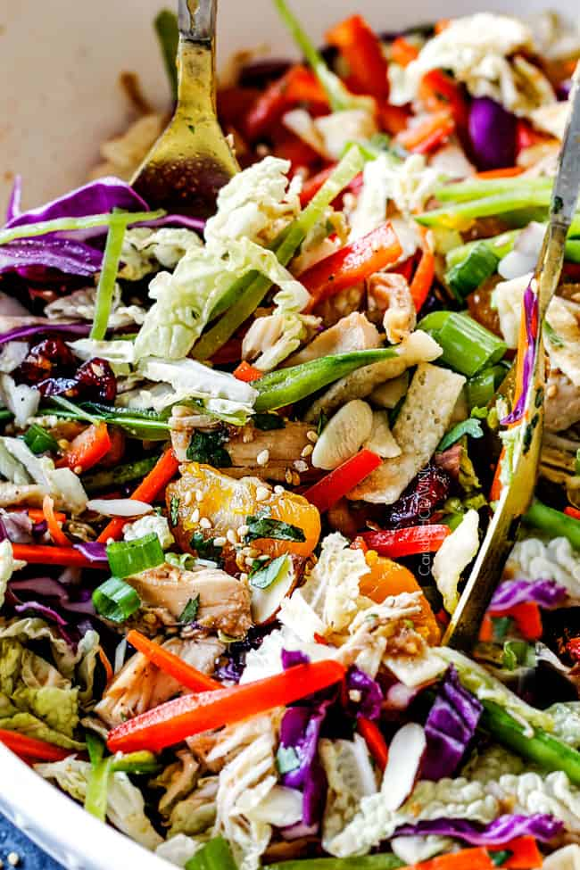 two tongs spooning healthy Chinese chicken salad tossed together with mandarin oranges, peanuts napa cabbage, wontons, carrots, snow peas, red bell peppers and sesame dressing