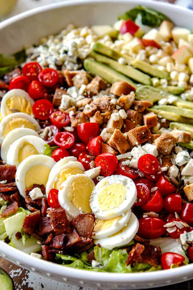 up close side view of Cobb salad with lettuce, hard boiled eggs, avocados, bacon, tomatoes and blue cheese