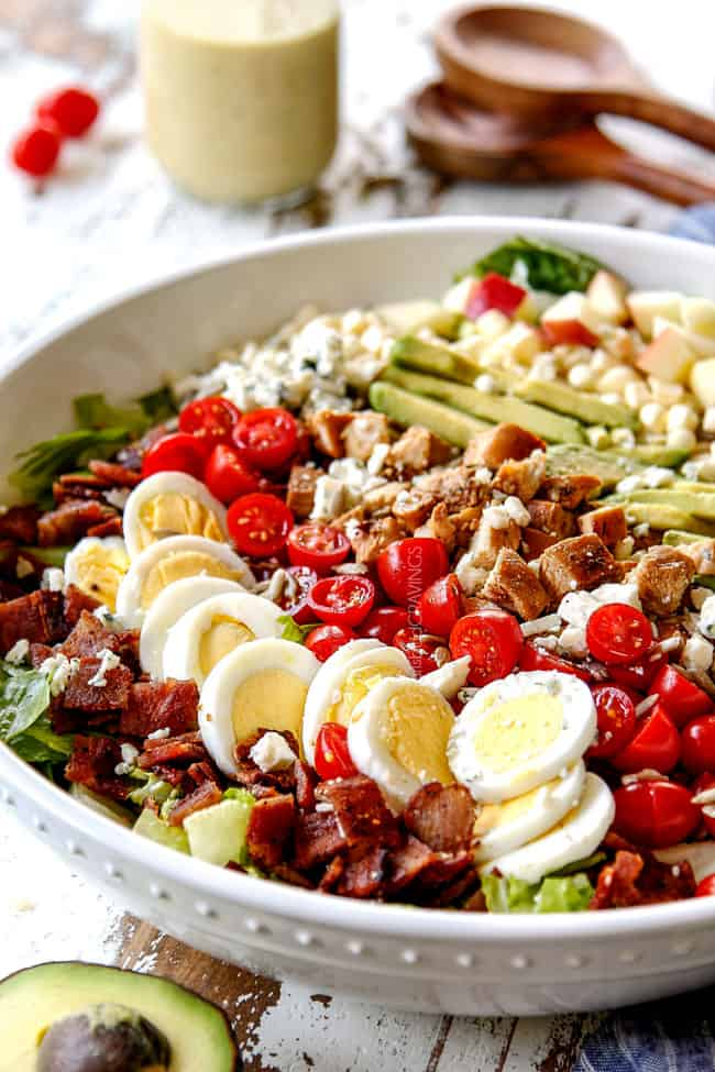 side far away view of Cobb salad with lettuce, hard boiled eggs, avocados, bacon, tomatoes and blue cheese