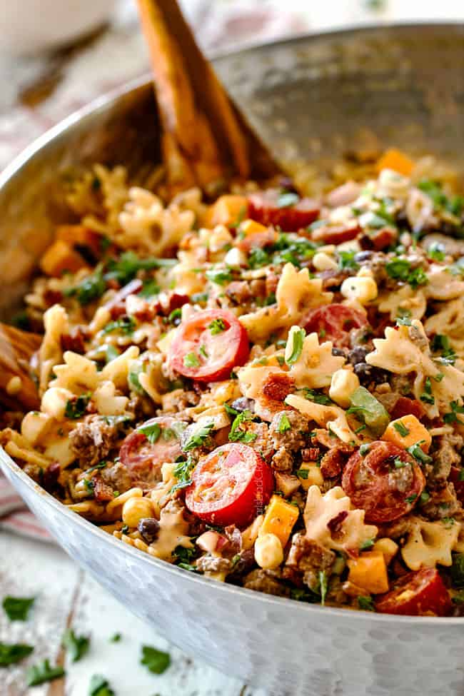 best Cowboy Pasta Salad with ground beef, black beans, corn, tomatoes and barbecue sauce in a metal bowl