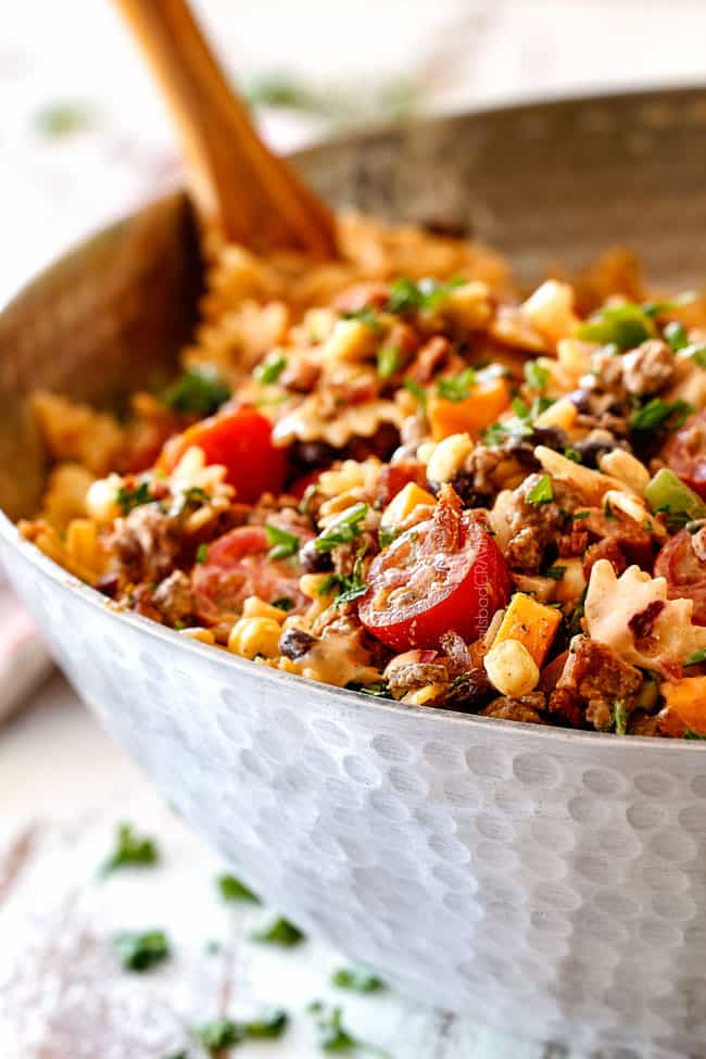 far away view of up close of Cowboy Pasta Salad with ground beef, black beans, corn, tomatoes and barbecue sauce in a metal bowl
