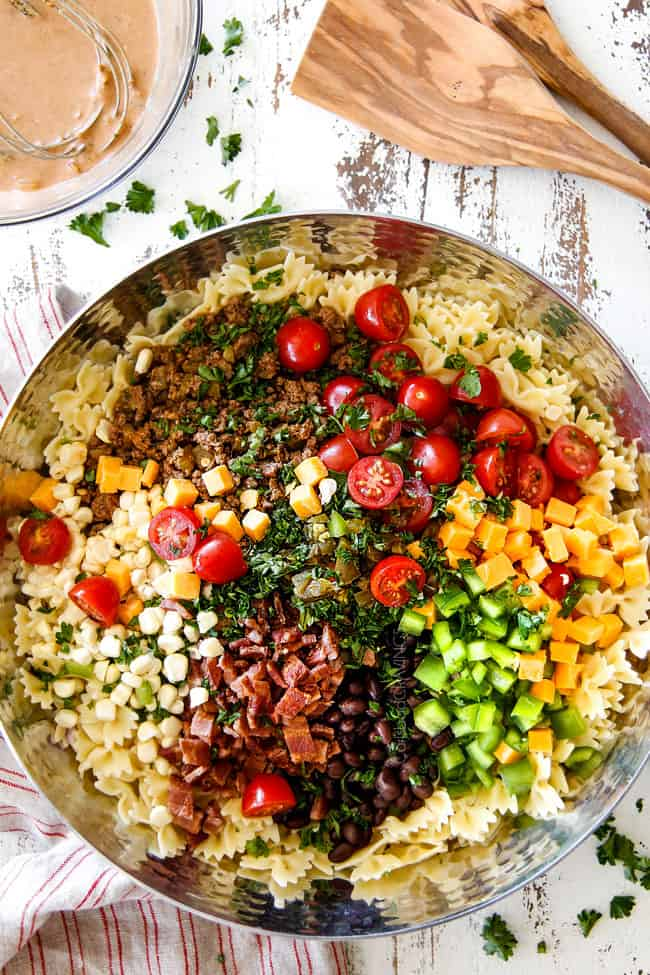 showing how to make Cowboy Pasta Salad by adding ground beef, black beans, corn, tomatoes, jalapenos, cilantro and barbecue sauce,
