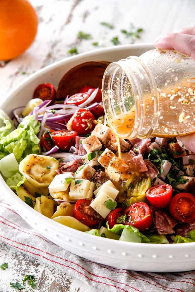 pouring the best dressing for pasta salad over salad in a white bowl
