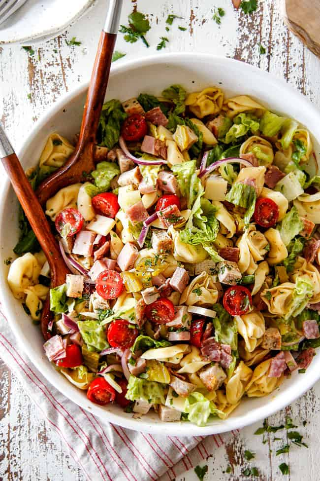 top view of pasta salad with cheesy tortellini, cubed pork roast, ham, salami, Swiss cheese, tomatoes, pickles pickled jalapenos, red onions, Romaine lettuce and cilantro