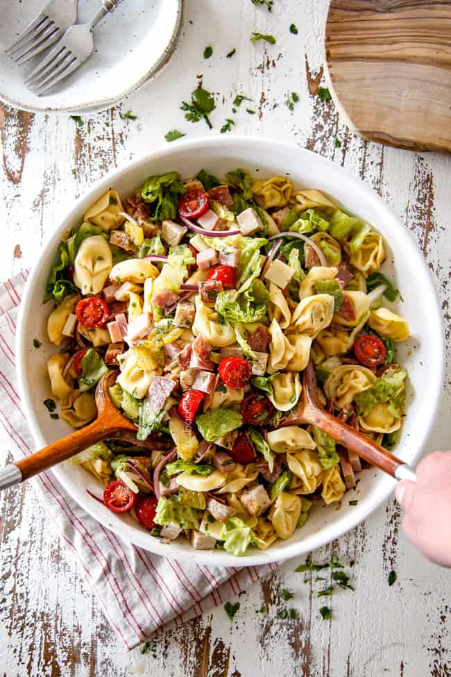 Top view of pasta salad with tongs tossing the pasta salad