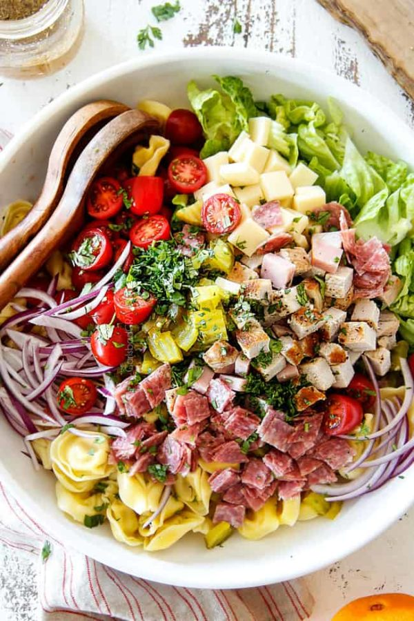 top view of Cuban pasta salad with cheesy tortellini, cubed pork roast, ham, salami, Swiss cheese, tomatoes, pickles pickled jalapenos, red onions, Romaine lettuce and cilantro