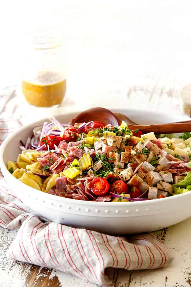 far away side view of Cuban pasta salad with cheesy tortellini, cubed pork roast, ham, salami, Swiss cheese, tomatoes, pickles pickled jalapenos, red onions, Romaine lettuce and cilantro