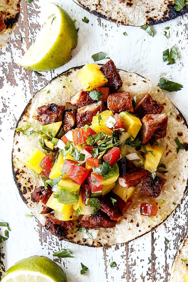 up close top view of al pastor pork on a corn tortilla with grilled pineapple, pico de gallo and avocado on a white board