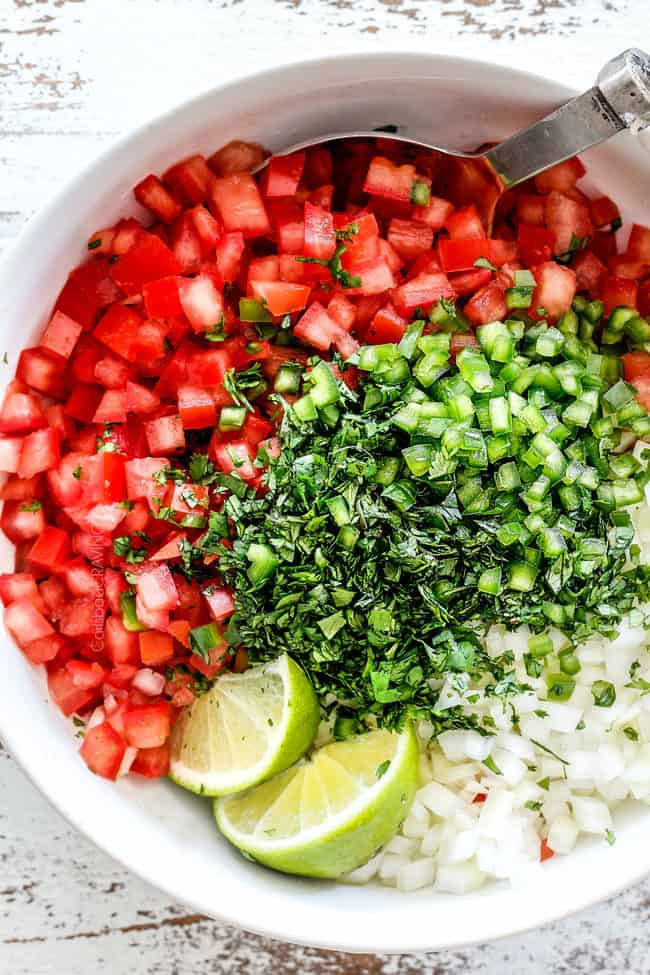 top view of tomatoes, cilantro, onions, jalapenos, lime juice in a white bowl for the best pico de gallo recipe