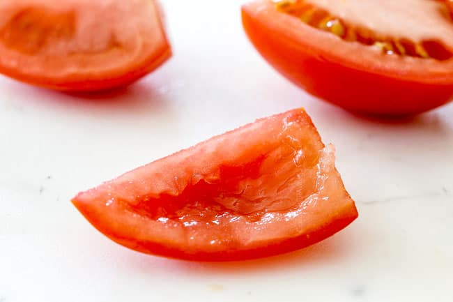 scooping out seeds of tomatoes showing how to make pico de gallo