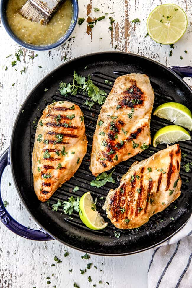 three pieces of Salsa Verde Chicken in a skillet with limes and cilantro