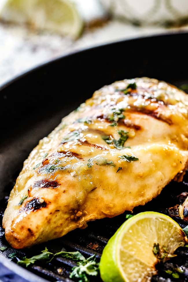 up close side view of salsa verde chicken in a black grill pan
