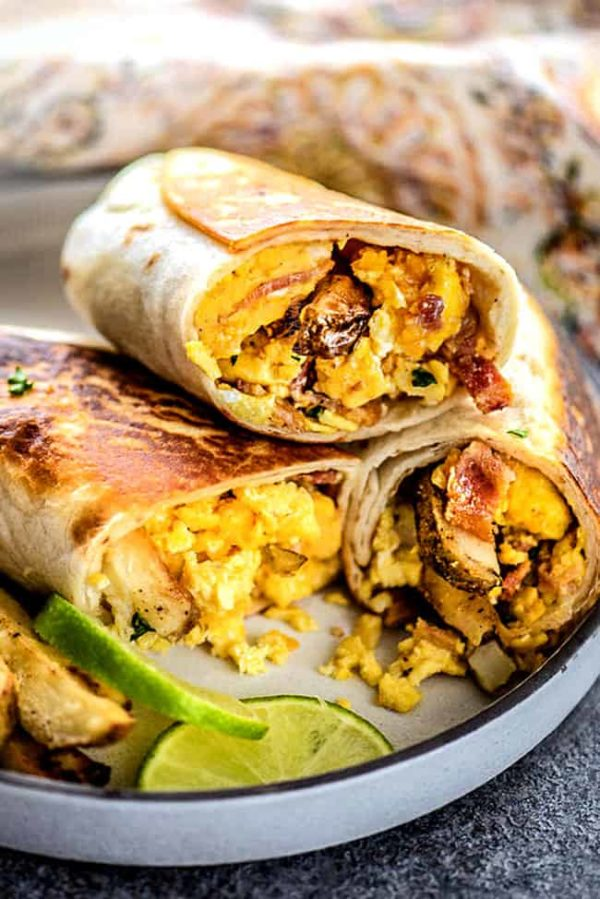 a plate of Mexican Breakfast Burritos sliced in half and stacked on a plate