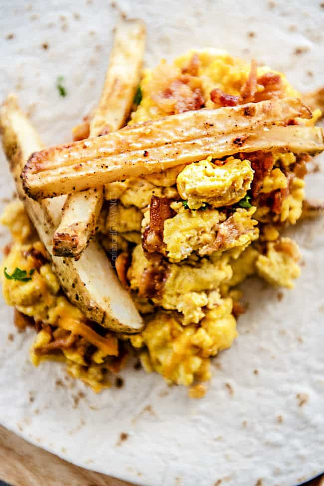 showing how to make easy breakfast burritos by piling a tortilla with eggs, cheese, bacon and french fries