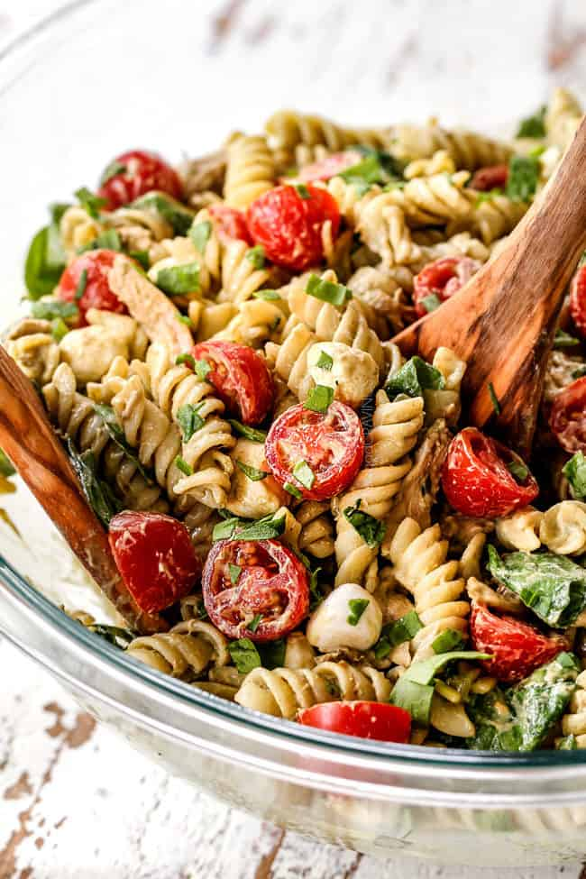 showing how to make Caprese Pasta Salad by tossing it with tongs.