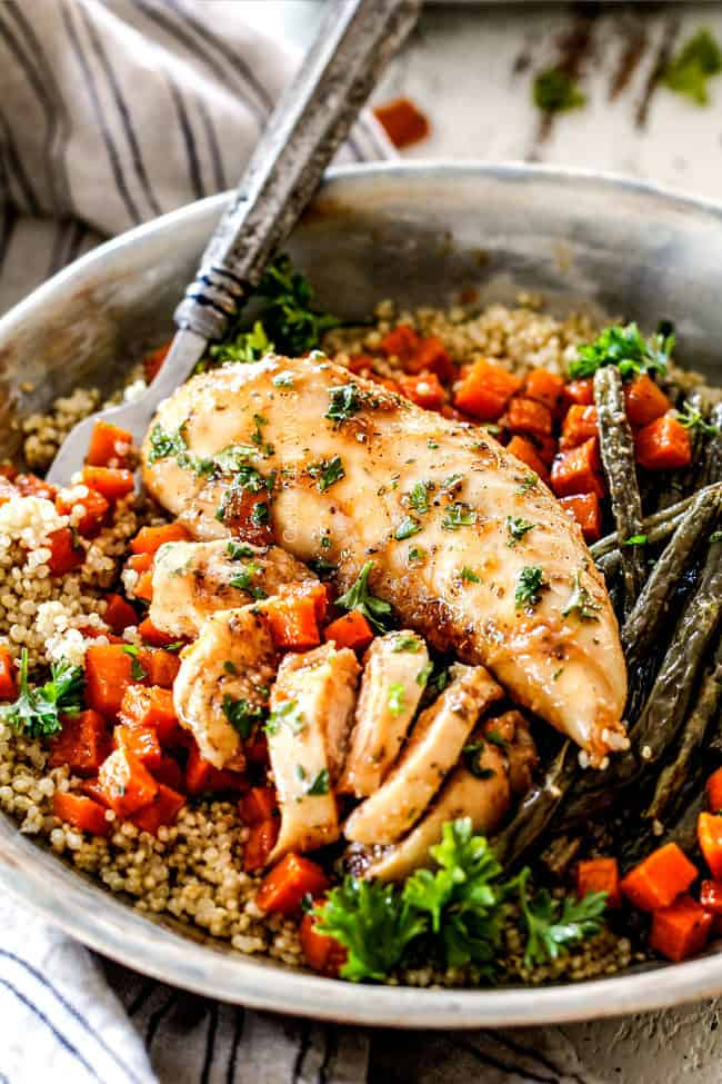 healthy sheet pan chicken and vegetables in a bowl with quinoa and a fork
