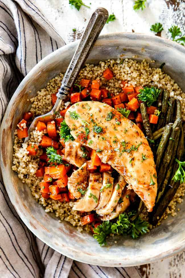 healthy sheet pan chicken and potatoes in a bowl with quinoa and a fork