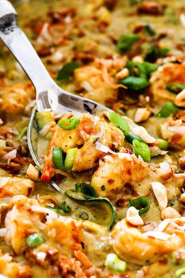 up close of Copycat Bang Bang Shrimp Bang Bang Shrimp in a large skillet with coconut, zucchini, peas, carrots