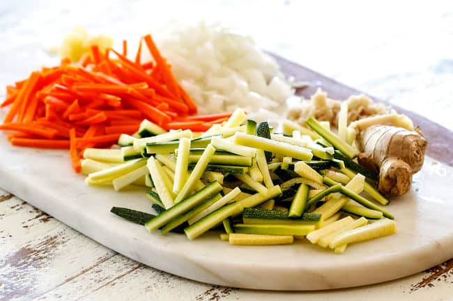 showing how to make Bang Bang Shrimp Copycat by cutting zucchini, carrots and onions