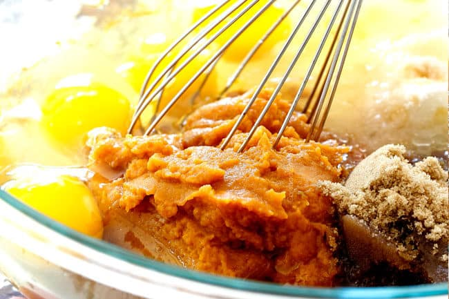 showing how to make best pumpkin bars by whisking the wet ingredients together in a glass bowl