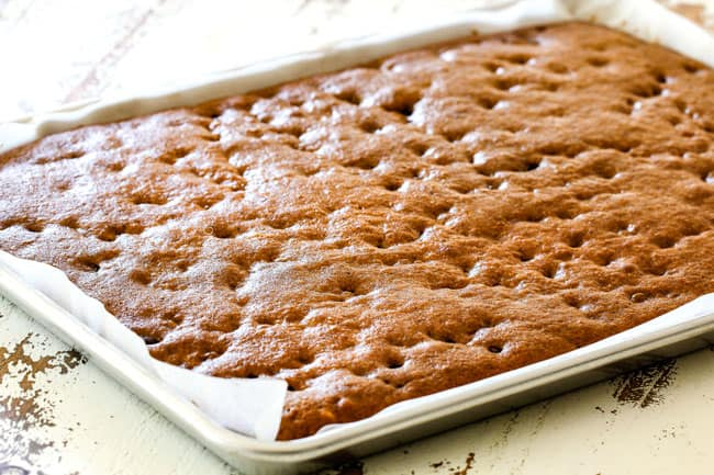 showing how to make pumpkin bars with cream cheese frosting by pulling the baked bars out of the oven