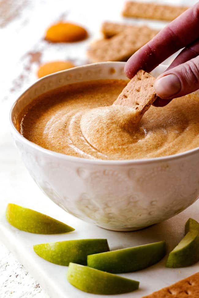 far away shot dipping a graham cracker into best pumpkin dip