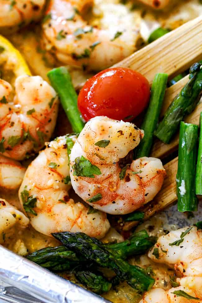 baked shrimp scampi without wine on a baking sheet being served with a wooden spoon