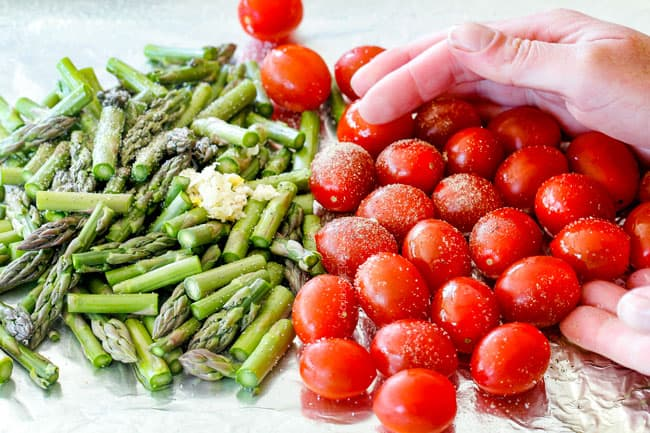 showing how to make Shrimp scampi in the oven by tossing tomatoes and asparagus on a baking sheet