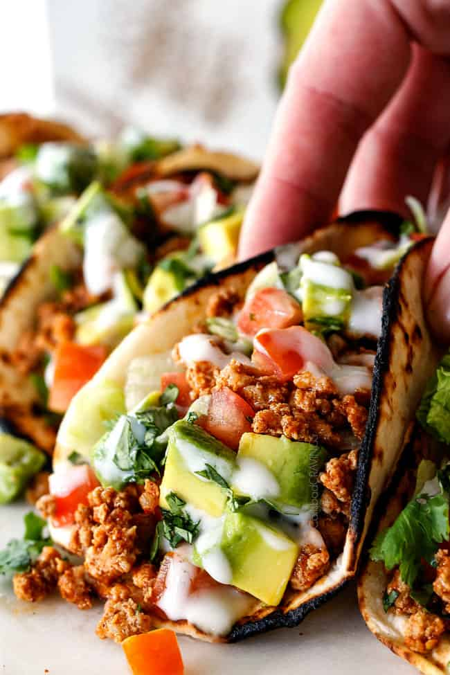 picking up a healthy turkey taco with ground turkey, taco seasoning, lettuce, sour cream, tomatoes and avocados