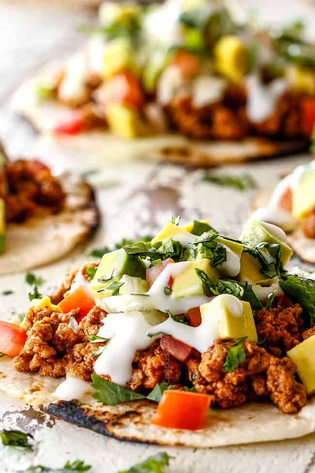 up close of healthy ground turkey taco laying with ground turkey, taco seasoning, lettuce, sour cream, tomatoes and avocados