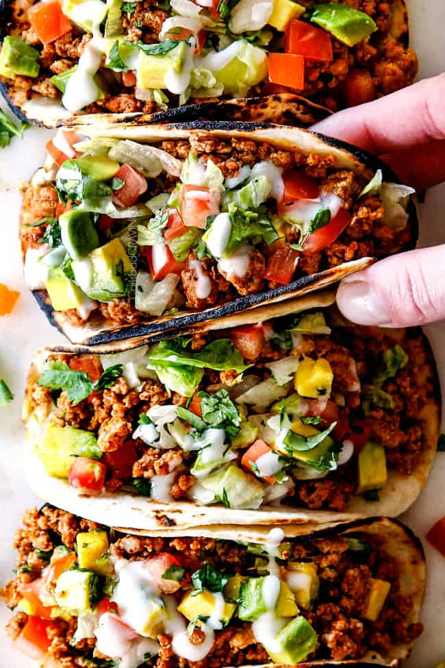 up close top view of a row of easy turkey taco with ground turkey, taco seasoning, lettuce, sour cream, tomatoes and avocados