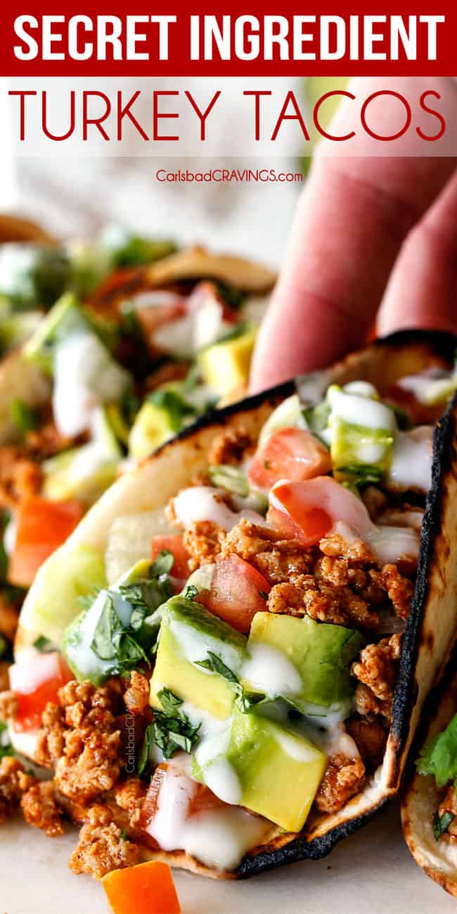 up close of picking up a healthy turkey taco with ground turkey, taco seasoning, lettuce, sour cream, tomatoes and avocados