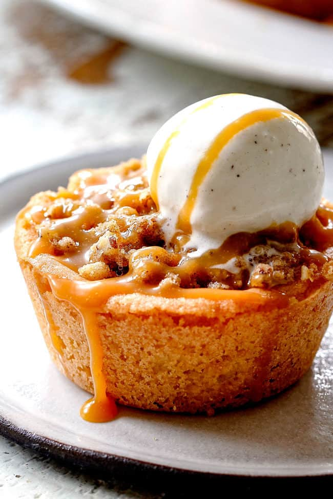 up close of caramel apple pie with streusel topping with ice cream and caramel dripping down the side