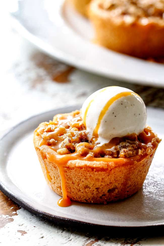 caramel apple pie with streusel topping with ice cream and caramel dripping down the side