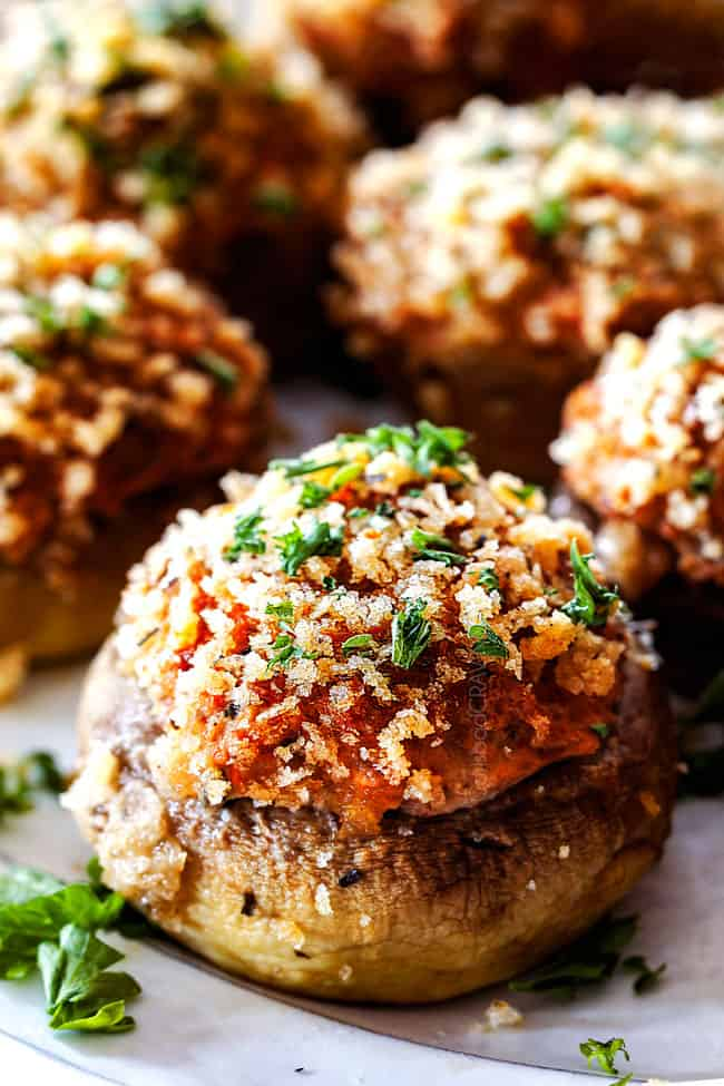 up close of easy Sausage Stuffed Mushrooms on a white serving plate