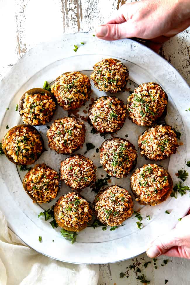 top view of easy sausage stuffed mushrooms on a white serving plate with cream cheese filling