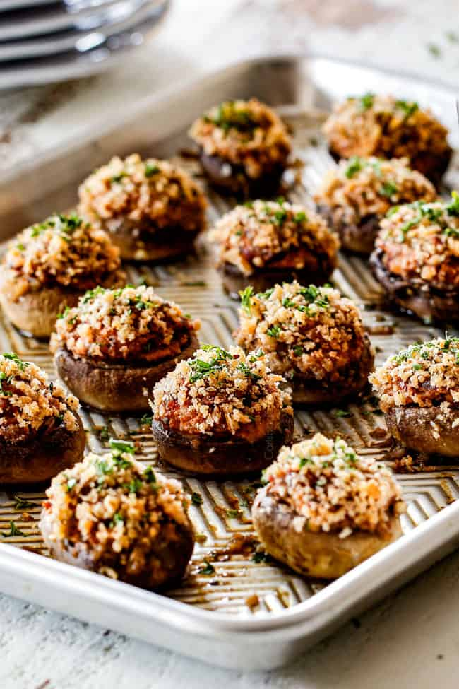 side view of rows of sausage stuffed mushrooms on a baking sheet